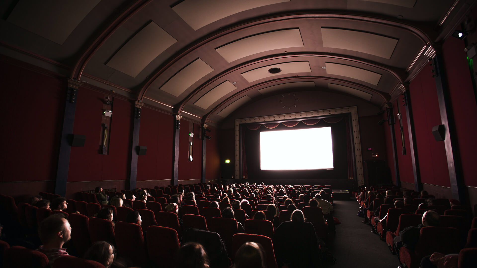 Image of Crowd in cinema theater with big white screen.